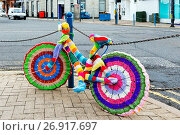 Купить «Bicycle with knitted covers, parked and secured against a chain fence next to a main road, Troon, Ayrshire.», фото № 26917697, снято 18 февраля 2020 г. (c) age Fotostock / Фотобанк Лори