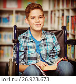 Купить «Portrait of disabled schoolboy holding book in library», фото № 26923673, снято 22 января 2019 г. (c) Wavebreak Media / Фотобанк Лори