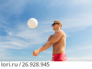 young man with ball playing volleyball on beach. Стоковое фото, фотограф Syda Productions / Фотобанк Лори
