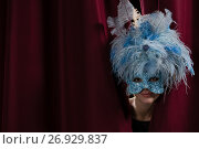 Купить «Female artist in masquerade mask peeking through the red curtain», фото № 26929837, снято 20 апреля 2017 г. (c) Wavebreak Media / Фотобанк Лори