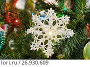 Купить «Вязаная снежинка на искусственной ёлке», эксклюзивное фото № 26930609, снято 3 января 2017 г. (c) Dmitry29 / Фотобанк Лори