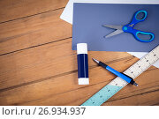 Купить «Directly above shot of scissor on papers with school supplies», фото № 26934937, снято 26 мая 2017 г. (c) Wavebreak Media / Фотобанк Лори