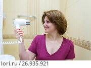 Купить «woman dries hair a hair dryer in a bathroom», фото № 26935921, снято 5 июня 2017 г. (c) Володина Ольга / Фотобанк Лори