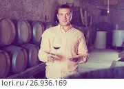 Купить «Customer holding glass of wine from wooden barrels», фото № 26936169, снято 22 сентября 2016 г. (c) Яков Филимонов / Фотобанк Лори