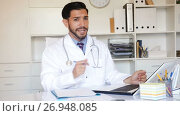 Купить «Spanish man doctor is working with documents behind laptop in his office.», видеоролик № 26948085, снято 9 августа 2017 г. (c) Яков Филимонов / Фотобанк Лори