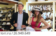 Купить «smiling adult woman and man trying on fashion hats in the shopping mall», видеоролик № 26949649, снято 16 мая 2017 г. (c) Яков Филимонов / Фотобанк Лори