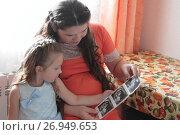 Мама показывает дочке результаты УЗИ (2017 год). Редакционное фото, фотограф Анатолий Матвейчук / Фотобанк Лори