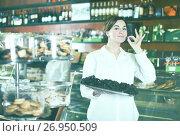 Купить «Seller offering tray of cakes», фото № 26950509, снято 24 января 2017 г. (c) Яков Филимонов / Фотобанк Лори