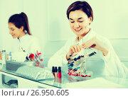 Купить «Female manicurist showing lacquer color schemes», фото № 26950605, снято 2 февраля 2017 г. (c) Яков Филимонов / Фотобанк Лори