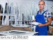Купить «Focused workman in overalls controlling quality of assembly of plastic window in workshop», фото № 26950821, снято 19 июля 2017 г. (c) Яков Филимонов / Фотобанк Лори