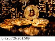 Золотые монеты криптовалюты Биткоин лежат на фоне электронной платы с микросхемами. Стоковое фото, фотограф Николай Винокуров / Фотобанк Лори