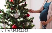 Купить «pregnant woman decorating christmas tree at home», видеоролик № 26952653, снято 14 сентября 2017 г. (c) Syda Productions / Фотобанк Лори
