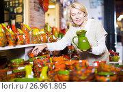Купить «Happy mature female choosing pottery cookware», фото № 26961805, снято 31 октября 2016 г. (c) Яков Филимонов / Фотобанк Лори