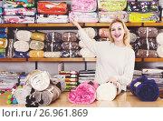 Купить «Female shop assistant demonstrating assortment of home textiles», фото № 26961869, снято 15 февраля 2017 г. (c) Яков Филимонов / Фотобанк Лори