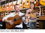 Купить «Couple playing guitars in music shop», фото № 26962009, снято 28 февраля 2020 г. (c) Яков Филимонов / Фотобанк Лори