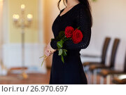 Купить «woman with red roses at funeral in church», фото № 26970697, снято 20 марта 2017 г. (c) Syda Productions / Фотобанк Лори