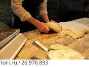 Купить «baker portioning dough with bench cutter at bakery», фото № 26970893, снято 15 мая 2017 г. (c) Syda Productions / Фотобанк Лори