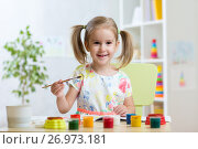 Купить «Smiling child girl painting in kindergarten», фото № 26973181, снято 30 сентября 2015 г. (c) Оксана Кузьмина / Фотобанк Лори