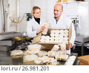 Different aged couple standing with box of turron in production workshop, фото № 26981201, снято 22 апреля 2017 г. (c) Яков Филимонов / Фотобанк Лори