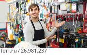 Купить «male seller posing at tooling section of household store», фото № 26981237, снято 18 ноября 2018 г. (c) Яков Филимонов / Фотобанк Лори