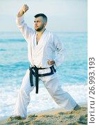 Купить «Guy doing karate poses at sunset sea shore», фото № 26993193, снято 19 июля 2017 г. (c) Яков Филимонов / Фотобанк Лори