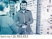 attentive male seller assisting woman in choosing door handles in shop. Стоковое фото, фотограф Яков Филимонов / Фотобанк Лори