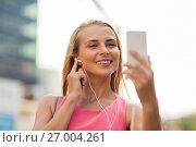 Купить «happy young woman with smartphone and earphones», фото № 27004261, снято 17 августа 2017 г. (c) Syda Productions / Фотобанк Лори