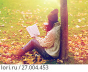 woman with book drinking coffee in autumn park. Стоковое фото, фотограф Syda Productions / Фотобанк Лори