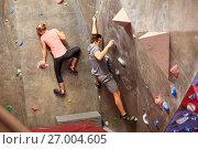 Купить «man and woman training at indoor climbing gym wall», фото № 27004605, снято 2 марта 2017 г. (c) Syda Productions / Фотобанк Лори