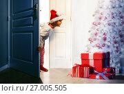 Купить «Boy checking presents under Christmas tree», фото № 27005505, снято 29 января 2017 г. (c) Сергей Новиков / Фотобанк Лори