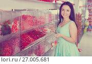 Купить «Pretty girl in sweets store picks up candies in bag», фото № 27005681, снято 25 апреля 2017 г. (c) Яков Филимонов / Фотобанк Лори