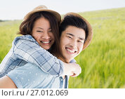 Купить «Millennial couple piggy back against blurry meadow», фото № 27012069, снято 18 октября 2018 г. (c) Wavebreak Media / Фотобанк Лори