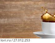 Купить «White cup with coffee splashing against blurry wood panel», фото № 27012253, снято 23 января 2019 г. (c) Wavebreak Media / Фотобанк Лори