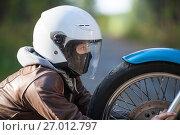 Купить «Женщина в мотошлеме рядом с колесом мотоцикла, крупный план», фото № 27012797, снято 24 сентября 2017 г. (c) Кекяляйнен Андрей / Фотобанк Лори
