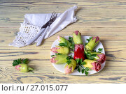 Купить «Cold appetizer with green peppers, bacon and sausage in the form of flowers on a wooden table close-up», фото № 27015077, снято 28 сентября 2017 г. (c) Татьяна Ляпи / Фотобанк Лори