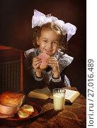 Купить «Первоклассница есть бутерброд с колбасой», фото № 27016489, снято 24 сентября 2017 г. (c) Марина Володько / Фотобанк Лори
