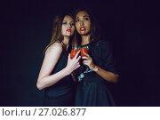 Купить «Attractive girls in the image of vampires hold glasses with blood. Halloween.», фото № 27026877, снято 22 сентября 2017 г. (c) Женя Канашкин / Фотобанк Лори