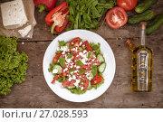 Купить «Shopska salad in a white plate on a wooden background, a number of raw ingredients lettuce. view from above.», фото № 27028593, снято 23 августа 2017 г. (c) Tetiana Chugunova / Фотобанк Лори