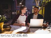 Купить «Young creative professionals talking while sitting with laptop at coffee shop», фото № 27036485, снято 21 мая 2017 г. (c) Wavebreak Media / Фотобанк Лори