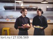 Купить «Smiling young wait staff looking at each other while holding fresh food in coffee shop», фото № 27036569, снято 21 мая 2017 г. (c) Wavebreak Media / Фотобанк Лори