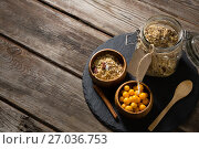 Купить «Bowl of cape gooseberry and jar of muesli on table», фото № 27036753, снято 13 июня 2017 г. (c) Wavebreak Media / Фотобанк Лори