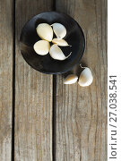 Купить «Garlics in plate on wooden table», фото № 27038541, снято 5 июня 2017 г. (c) Wavebreak Media / Фотобанк Лори