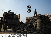 Купить «Bangladeshi child laborers handle pieces of old tyres to be recycled in Dhaka. The recycling industry in the Bangladeshi capital plays an important role...», фото № 27039769, снято 15 марта 2015 г. (c) age Fotostock / Фотобанк Лори