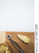 Directly above view of peeler and fresh ginger on wooden cutting board. Стоковое фото, агентство Wavebreak Media / Фотобанк Лори