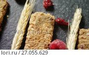 Купить «Granola bars with barley and raspberry on concrete background 4k», видеоролик № 27055629, снято 24 января 2020 г. (c) Wavebreak Media / Фотобанк Лори