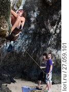Купить «Скалолаз со страховочной веревкой напряженно поднимается вверх по отвесной стене а его товарищи обеспечивают безопасность», фото № 27059101, снято 15 декабря 2010 г. (c) Эдуард Паравян / Фотобанк Лори