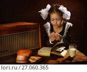 Купить «Первоклассница ест бутерброд с колбасой», фото № 27060365, снято 24 сентября 2017 г. (c) Марина Володько / Фотобанк Лори