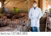 Купить «Veterinarian in mask holding syringe and bottle», фото № 27061053, снято 21 октября 2018 г. (c) Яков Филимонов / Фотобанк Лори