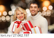 Купить «happy couple in sweaters holding christmas gifts», фото № 27062197, снято 7 октября 2012 г. (c) Syda Productions / Фотобанк Лори