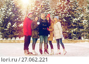 happy friends with smartphone on ice skating rink. Стоковое фото, фотограф Syda Productions / Фотобанк Лори